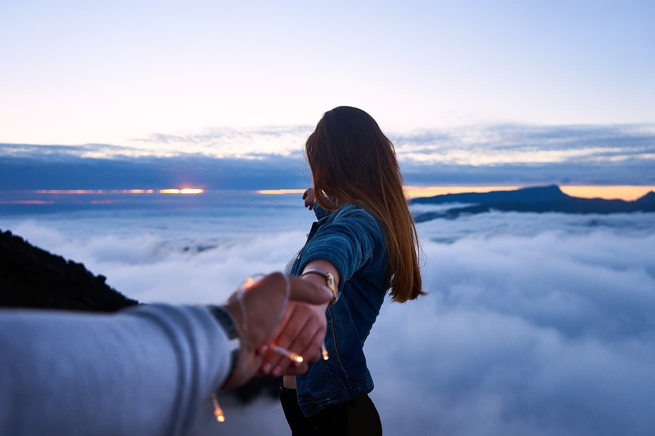 local landscaper holding hands with his girlfriend infront of clouds